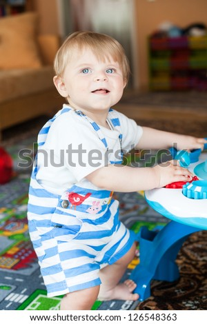 Little toddler boy playing with  toys indoor