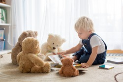 Little toddler boy, reading a book to his teddy bear friends at home, sitting in living room