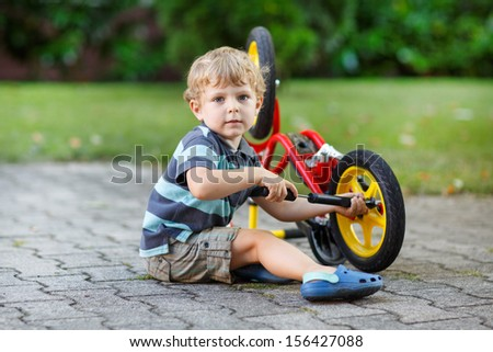 Little toddler boy repairing his first bike