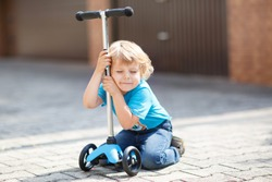 Little toddler boy riding and his scooter bicycle in summer