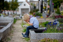 Little toddler boy, sitting on a grave in cemetery, sad and lonely