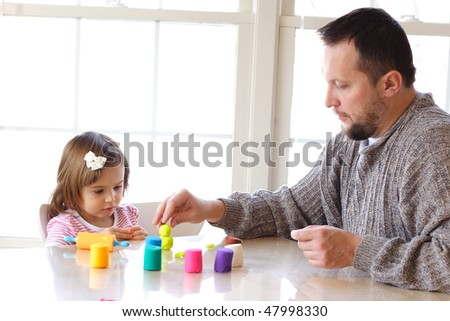 Little toddler girl and father creating toys from playdough - stock photo