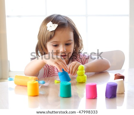 Little toddler girl creating toys from playdough