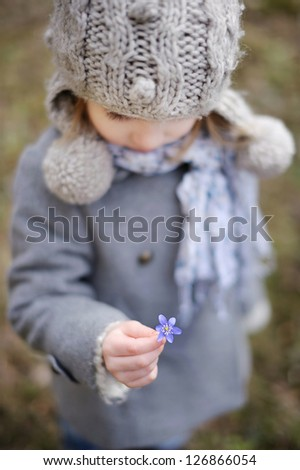 Little toddler girl holding a first flower of spring