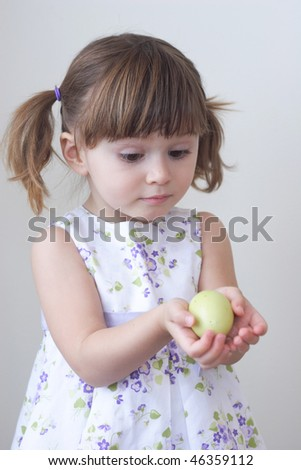 Little toddler girl holding a hand painted egg in her hands