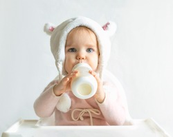 Little toddler girl in a warm fluffy hat drinks milk from a bottle while sitting. Half-length portrait. White gray background.