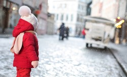 Little toddler girl in beautiful warm red outfit playing outdoors in the snow