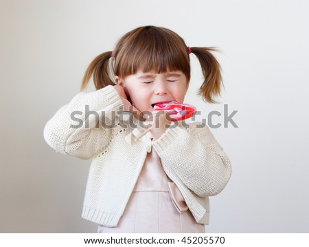 Little toddler girl is biting a large piece of hard candy