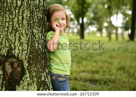Little toddler girl playing on the park with a green leaf