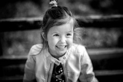 Little toddler girl portrait. Smiling kid. Happy childhood concept. Long hair baby. Laughing child. Monochrome portrait of children.