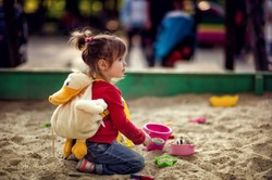 Little toddler girl sitting and playing in sandbox outdoors in park. Active child. People concept.