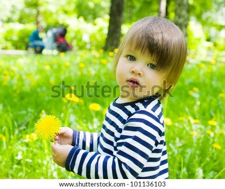 Little toddler girl walk outdoors and holding yellow flower dandelions