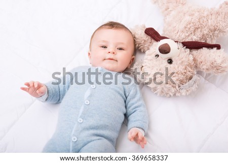 Stock Photo Little toddler is lying in bed with his toy.