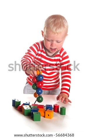 Little toddler is playing with colorful wooden beads
