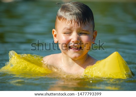 little toddler kid swimming in lake with inflatable arms aids support summer lake