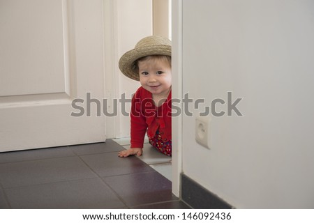 little toddler playing hide and seek , inside