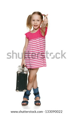 Little tourist. Little girl with old fashioned suitcase showing thumb up sign