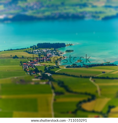 Little town on the coast of a lake surrounded by green fields. Germany #711010291