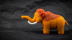 little toy mammoth isolated on dark background
