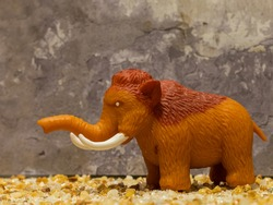 little toy mammoth on rocky background