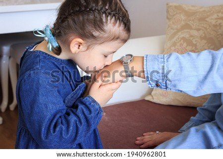 Little Turkish girl is kissing her mother's hand in ramadan feast. Traditional ritual in holy holidays. Muslim asian kid is wearing blue clothes in holy ramadan holiday.