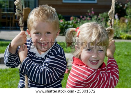 stock photo : Little twins playing on a swing