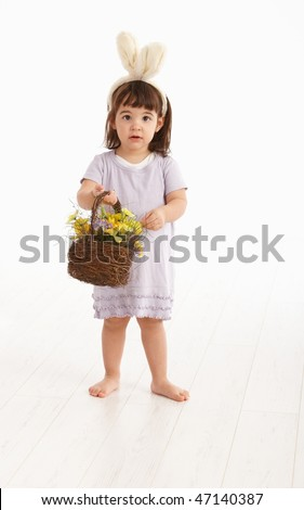 Little two years old girl wearing Easter bunny ears, isolated on white background.