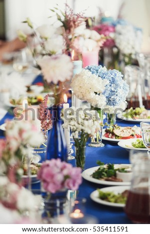 Little Vases With Field Flowers And Hydrangeas Stand On Blue Dinner