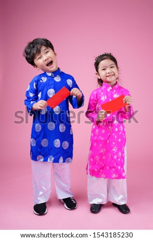 Little Vietnamese boy and girl holding red envelops for Tet. The word mean double happiness. It is the gift in lunar new year or Tet Holiday on isolate background