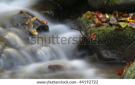 Little waterfall in the forest at autumn