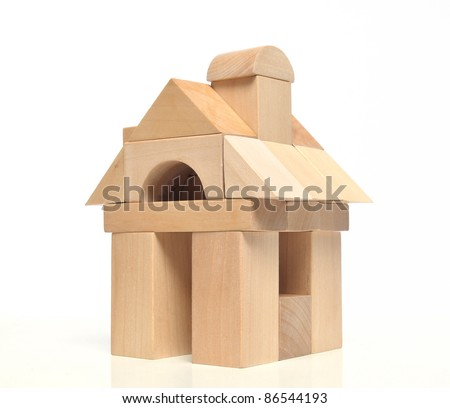Little weekend house with natural colored toy blocks on white background