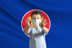 Little white boy in a protective mask on the background of the flag of Association of Southeast Asian Nations. Makes a stop sign with his hands, stay at home Association of Southeast Asian Nations.