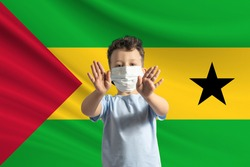 Little white boy in a protective mask on the background of the flag of Sao Tome and Principe. Makes a stop sign with his hands, stay at home Sao Tome and Principe.