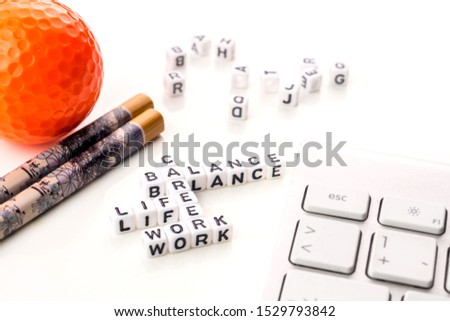 little white dices with black letters forming a crossword with the theme work life balance as equilibrium of professional and personal family life with tools on white background