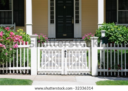 Little white gate and picket fence with roses. Frontal view, high contrast, porch and house facade in background