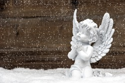 little white guardian angel in snow on wooden background. vintage style christmas decoration with falling snowflakes effect