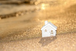 Little white house model on the sand on sea wave and sunlight background. Dream life home concept. Golden beach with sunrays and sweet home, selective focus