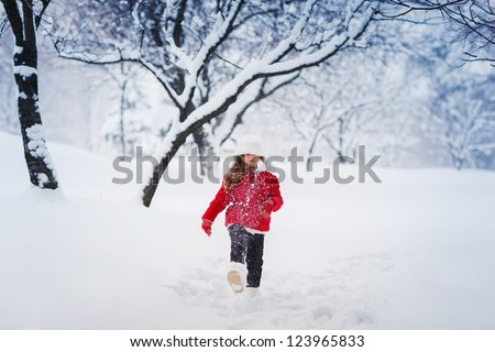 Little winter girl in fairy ice forest smiling
