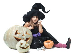 Little witch sits near the pumpkins and eating candy