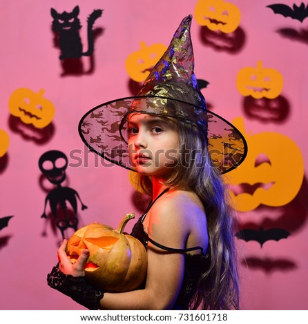 Little witch wearing black hat. Girl with calm face on pink background with bats and pumpkins decor. Halloween party and decorations concept. Kid in spooky witches costume holds carved pumpkin #731601718