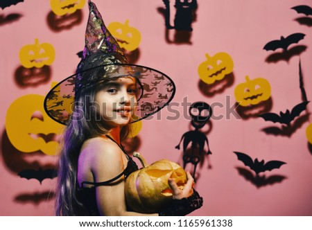 Little witch wearing black hat. Halloween party and decorations concept. Girl with smiling face on pink background with bats and pumpkins decor. Kid in spooky witches costume holds carved pumpkin #1165961338