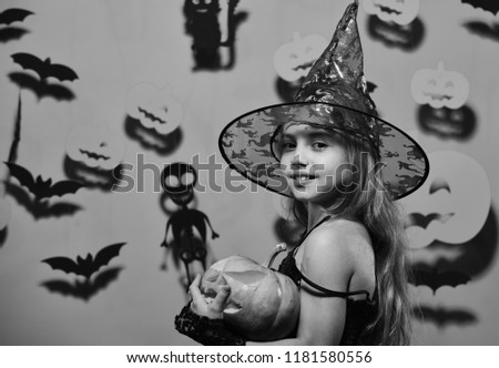 Little witch wearing black hat. Halloween party and decorations concept. Girl with smiling face on pink background with bats and pumpkins decor. Kid in spooky witches costume holds carved pumpkin #1181580556