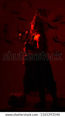 Little witch wearing black hat. Kid in spooky witches costume holds candlestick and old clock. Girl with curious face on bloody red background with decor. Halloween party and decorations concept #1165393546