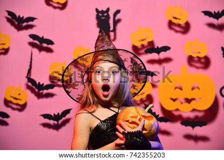 Little witch wearing black hat. Kid in spooky witches costume holds carved pumpkin. Halloween party and decorations concept. Girl with surprised face on pink background with bats and pumpkins decor #742355203