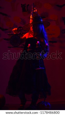 Little witch wearing black hat. Kid in spooky witches costume holds clock and chandelier. Halloween party concept. Girl with hidden face on bloody red background with bats and pumpkins decor #1178486800