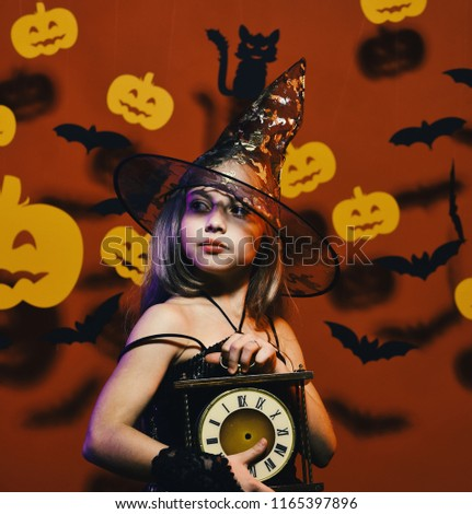 Little witch wearing black hat. Kid in spooky witches costume holds old clock. Girl with proud face on bloody red background with bats and pumpkins decor. Halloween party and decorations concept #1165397896