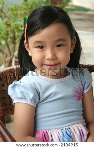 Little with pony-tail smiling and sitting on a rattan chair