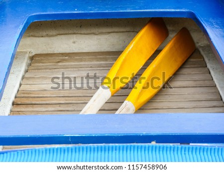 Little wooden blue boat with yellow paddles  #1157458906