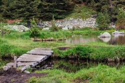 Little wooden bridge in a glare, over a placid lake in the Italian Alps