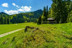 little wooden chapel on the hill next the high moor in Bregenz forest, with trees, forests and mountains in background. spring, Vorarlberg, Austria. shingled chapel with little tower at a sunny day